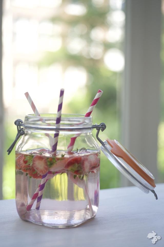 Het beste wapen in de strijd tegen frisdrank is water. Hoe maak je water leuker? Met aardbeienkroontjes, die je toch overhoudt als je aardbeien koopt. Gooi ze in een weckfles of tapfles (of in een paar jampotjes), water erbij en een uurtje laten trekken. Dan eventueel een uurtje de koelkast in. Het water wordt heel licht roze en krijgt een subtiele aardbeiensmaak. Onze kinderen noemen het 'Smaakwater' en bedachten dat het leuk is om het met z'n allen uit de weckfles te drinken, dus huppakee, iedereen een rietje erin. En reken maar dat het snel op gaat. Behalve gezellig om te doen, is Smaakwater een prima manier om kinderen aan subtiele smaken te laten wennen. Ook zonder scheppen suiker kun je op een lekkere, vrolijk manier je dorst lessen. Een beetje Zomerkoning gooit z'n kroon niet weg, maar maakt er aardbeienwater van.